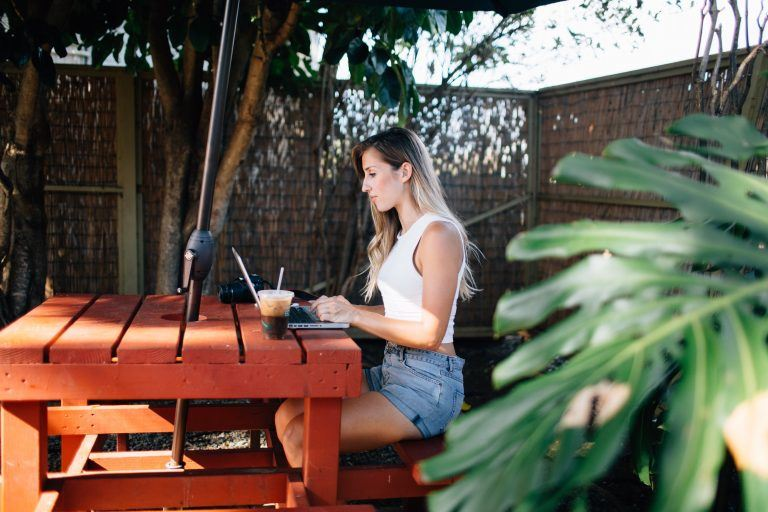 Elise Darma working on laptop sitting at a picnic table