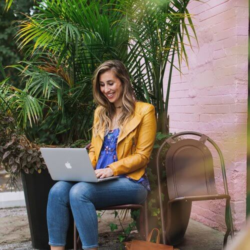 Elise Darma smiling and working on a laptop with a palm tree in the background