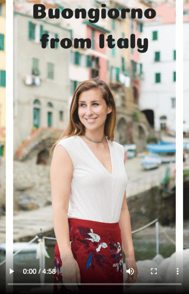 Buongiorno from Italy - Elise Darma smiling in front of colourful buildings.