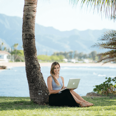 Elise Darma sitting with a laptop in front of a palm tree